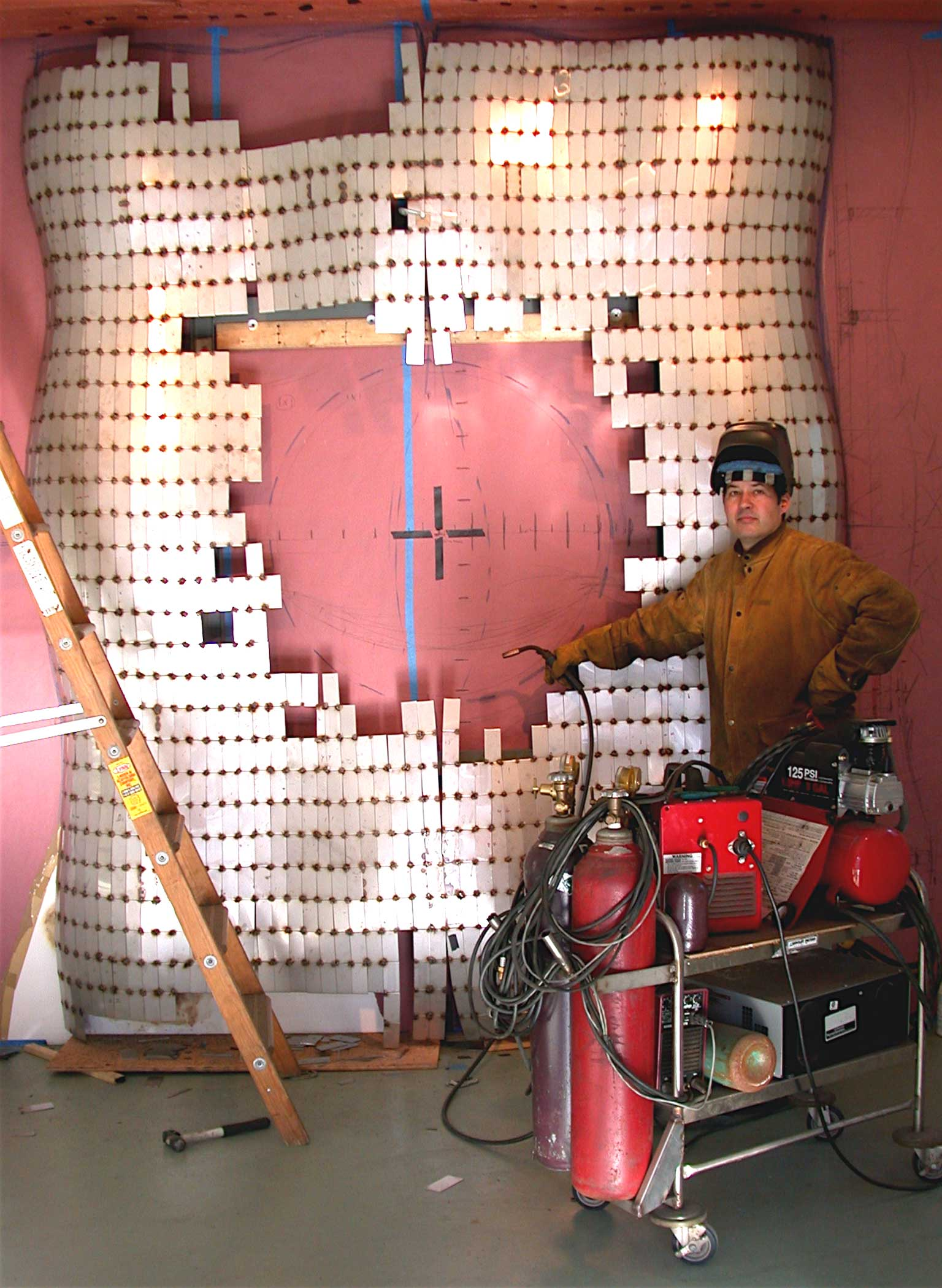 Peter Diepenbrock fabricating a large stainless steel sculptural wall piece