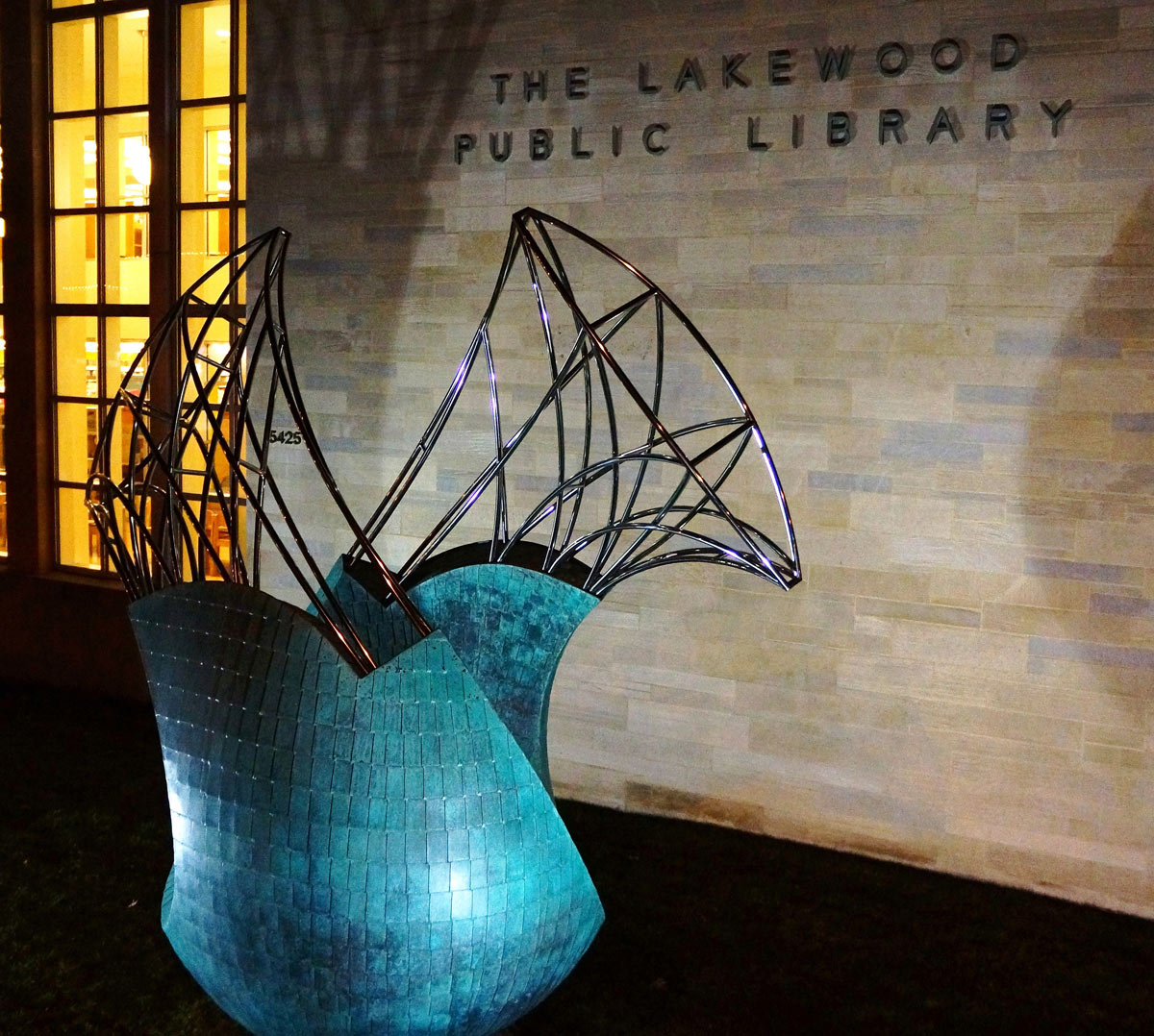 Transversion at night a  bronze and stainless public sculpture by Peter Diepenbrock Lakewood Ohio